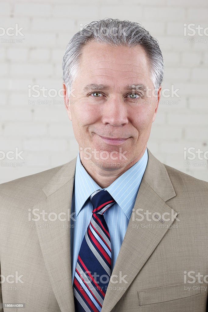Smiling middle age man with tan suit and tie royalty-free stock photo