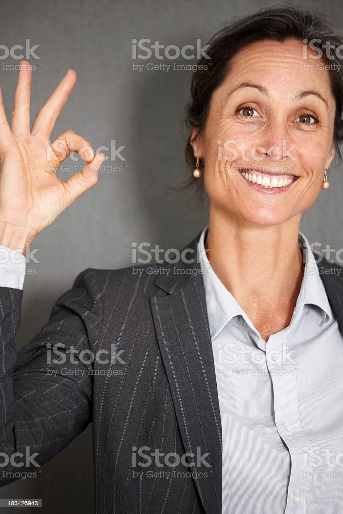 Smiling, middle aged businesswoman showing okay sign royalty-free stock photo