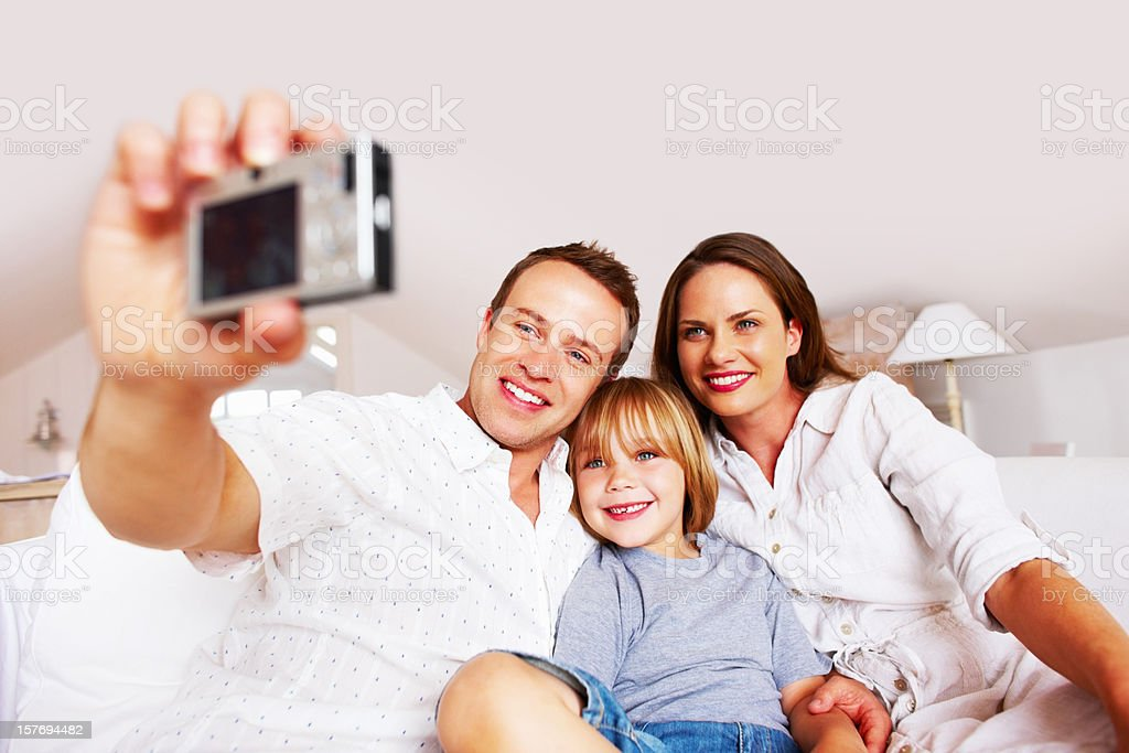 Smiling middle aged man taking a photo of his family royalty-free stock photo