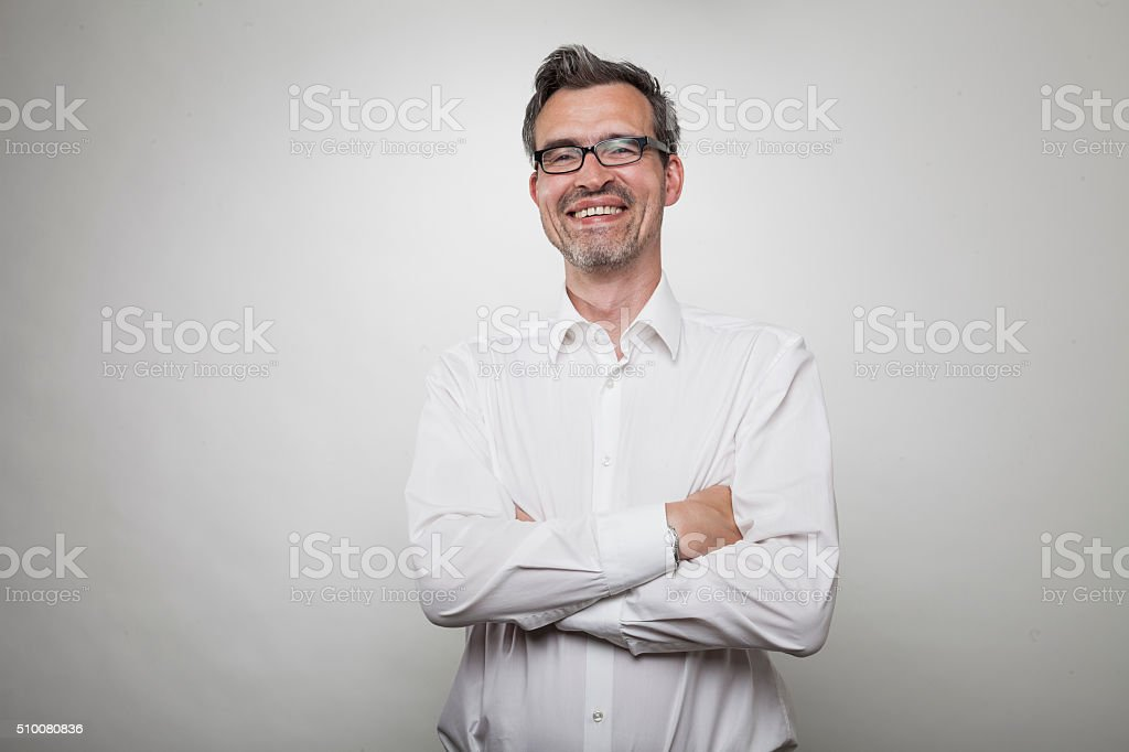 smiling middle aged manager with crossed arms in white shirt stock photo