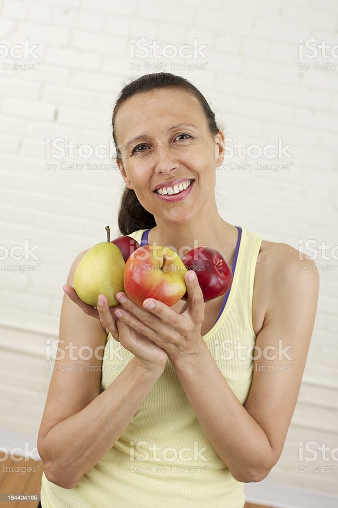 Smiling middle-aged woman holding fruit stock photo