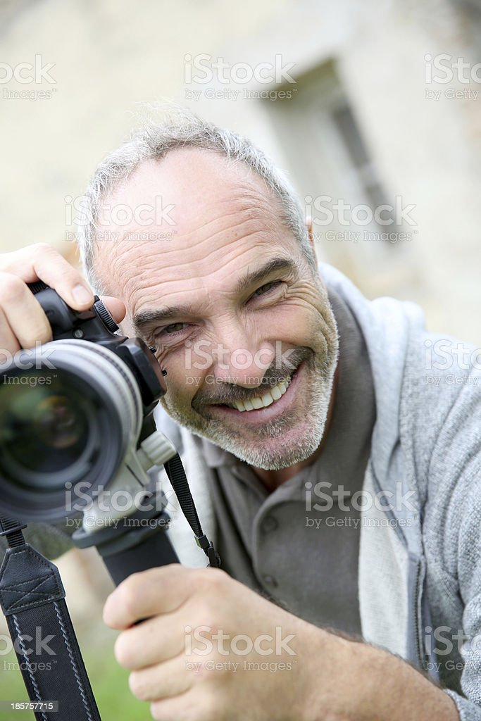 Smiling midlle-aged man taking picture with camera royalty-free stock photo