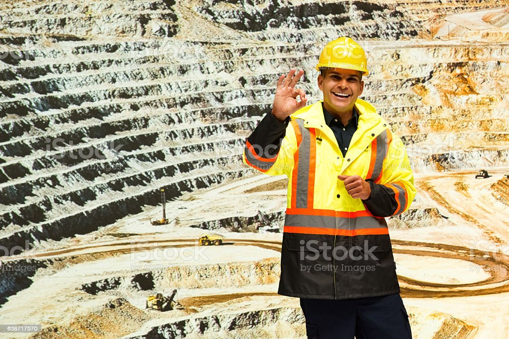 Smiling miner giving ok sign in mine stock photo