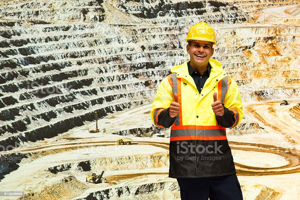 Smiling miner giving thumbs up at the mine stock photo