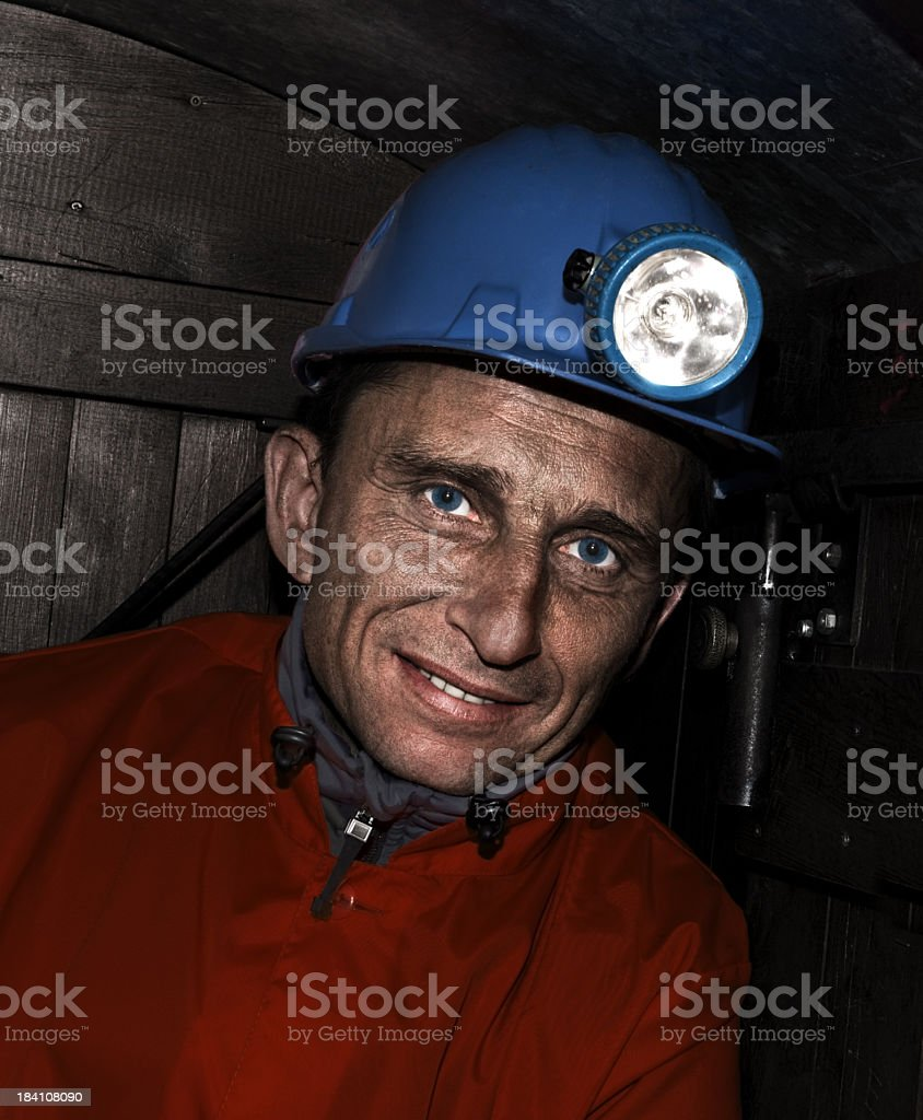 Smiling miner with blue eyes wearing blue helmet with light stock photo