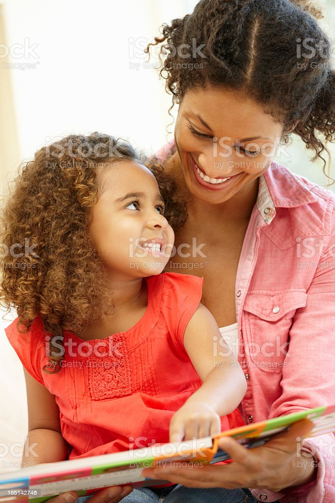 Smiling mixed race woman and young daughter reading a book stock photo