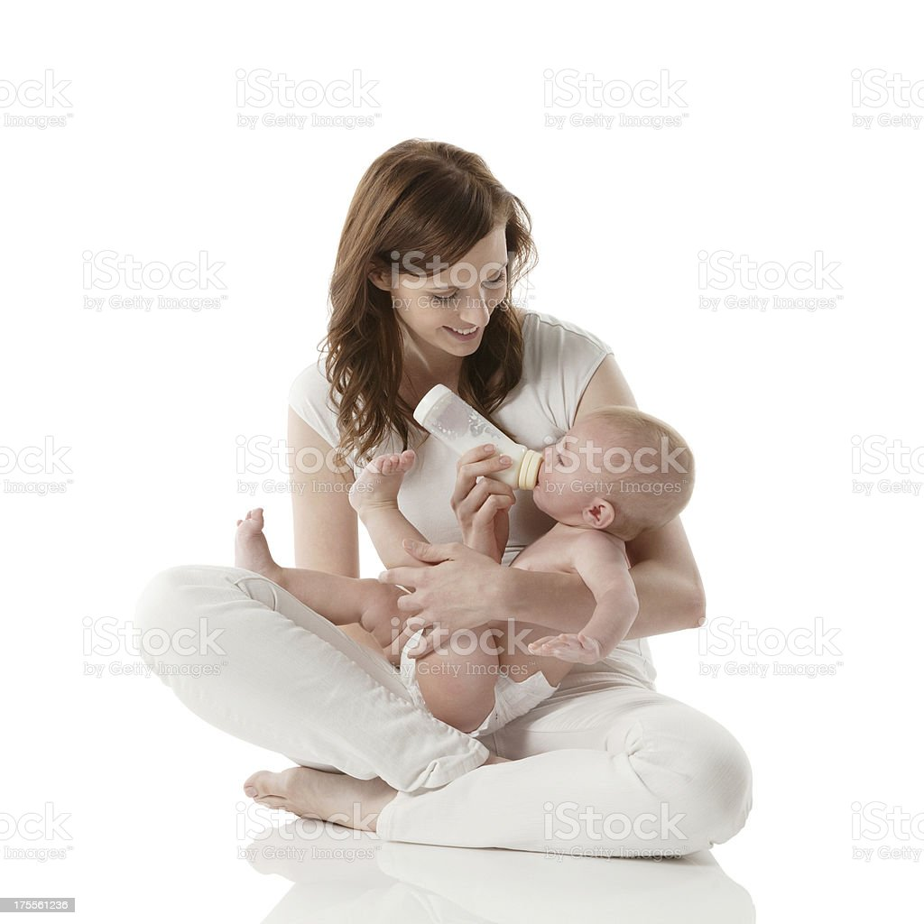 Smiling mom feeding her baby with milk royalty-free stock photo