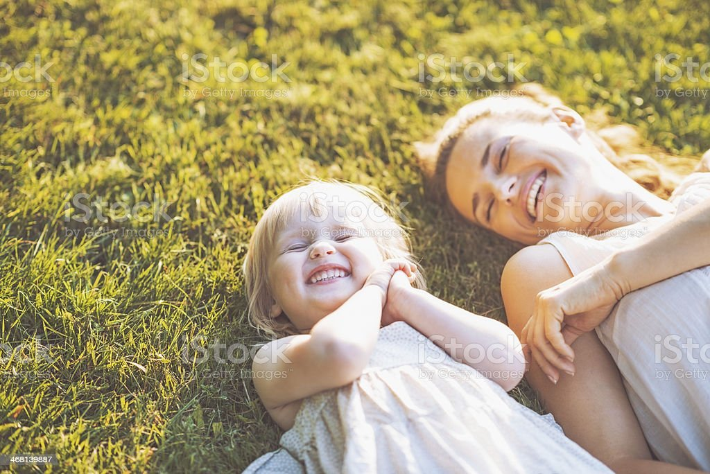 smiling mother and baby laying on meadow stock photo