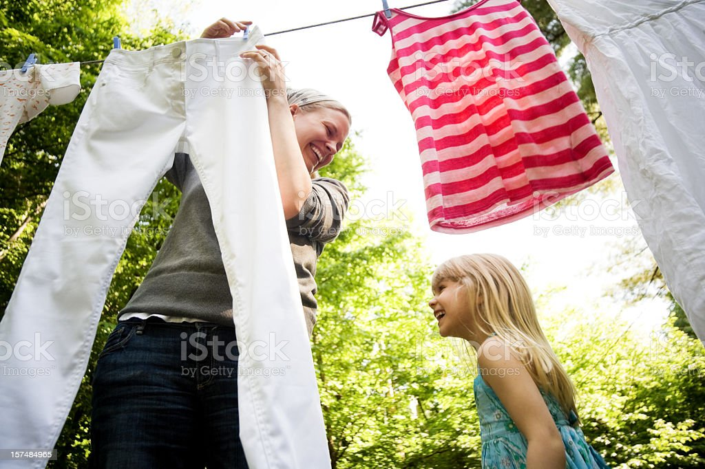 Smiling mother and child hanging clothes outside together stock photo