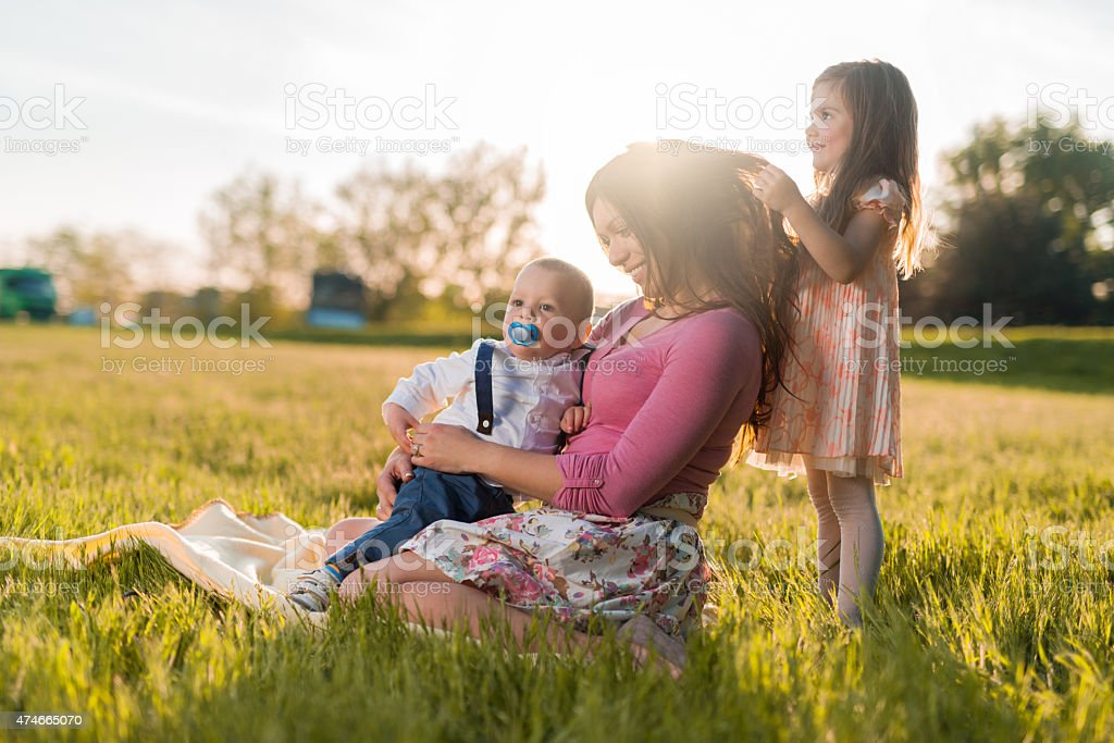 Smiling mother and children spending a spring day in nature. stock photo