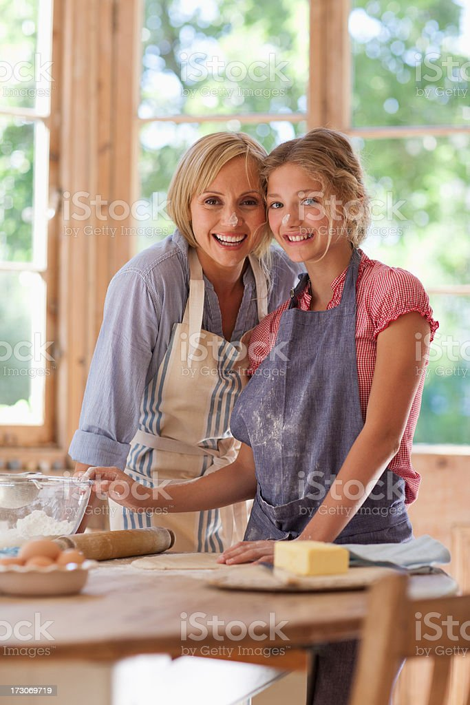 Smiling mother and daughter hugging and baking in kitchen stock photo