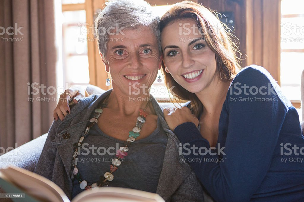 Smiling mother and daughter reading a book together stock photo