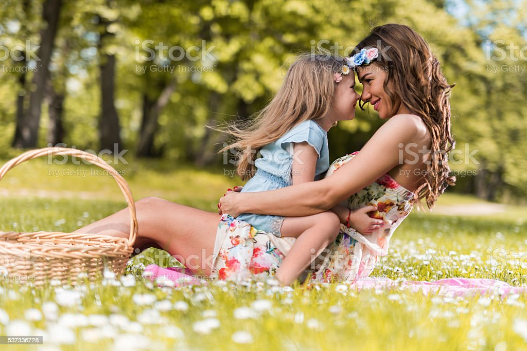 Smiling mother and daughter showing affection in the park. stock photo