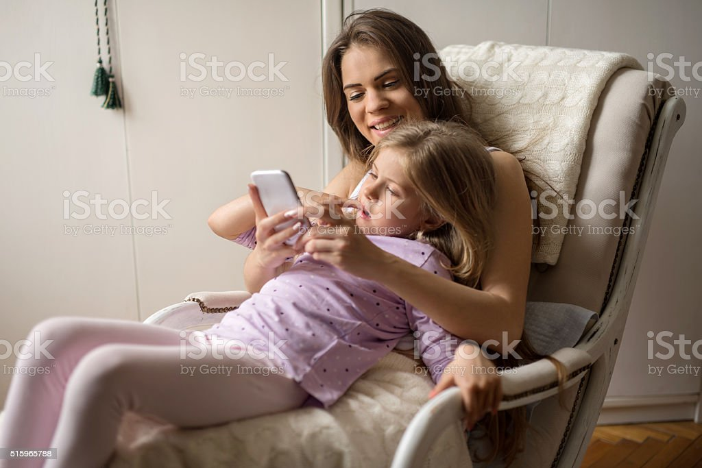 Smiling mother and daughter using mobile phone at home. stock photo