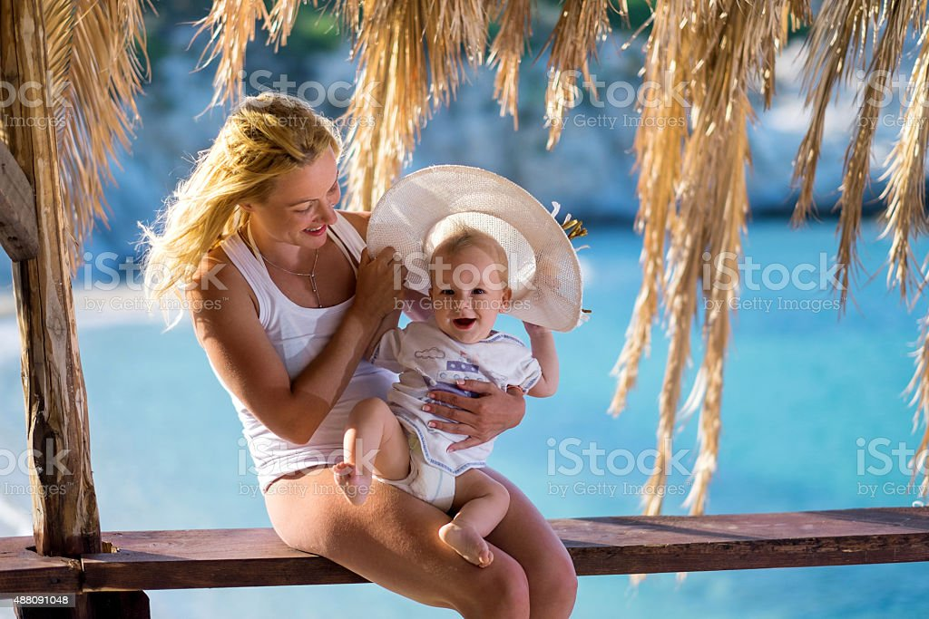 Smiling mother and her baby son enjoying in summer vacation. stock photo