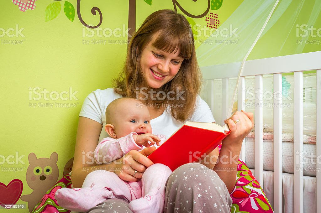 Smiling mother and her child reading a book stock photo