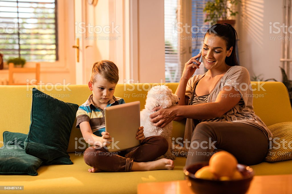 Smiling mother and her son using wireless technology at home. stock photo