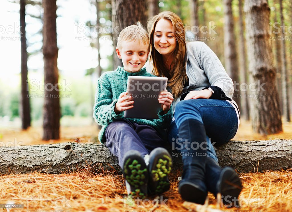 Smiling mother and son with new tablet-style computer in forest stock photo