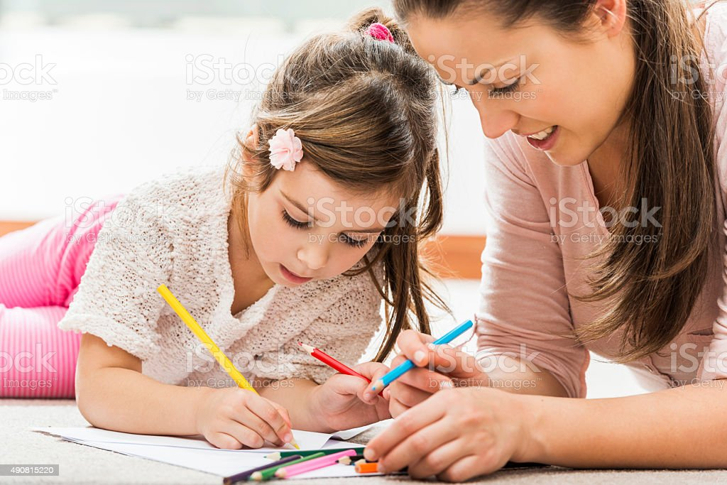 Smiling mother coloring with her daughter at home stock photo