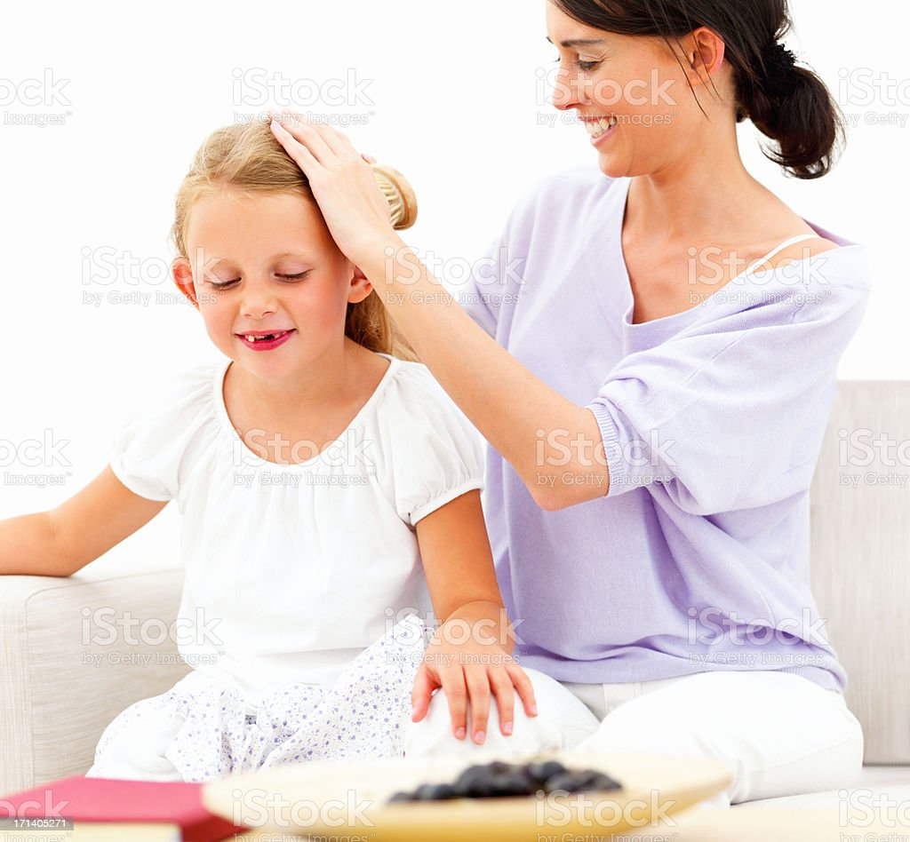 Smiling mother combing hair of daughter at home royalty-free stock photo