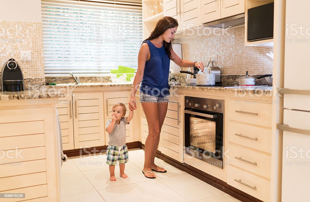 Smiling mother cooking lunch for her little son. stock photo