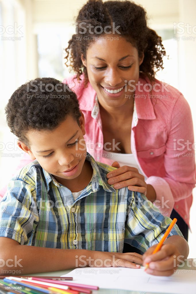Smiling mother helping her son with his homework royalty-free stock photo