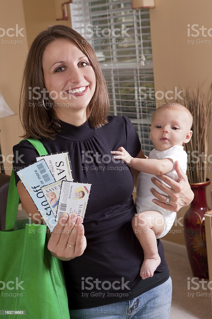 Smiling Mother Holding Baby And Coupons royalty-free stock photo