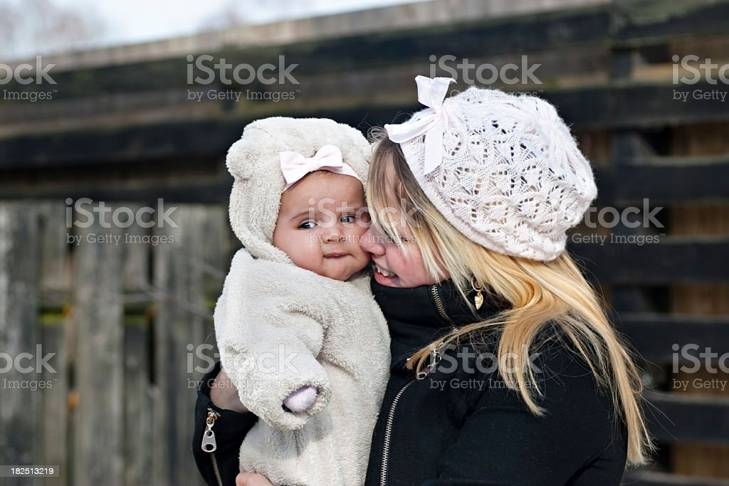 Smiling mother holding her baby outside on a cold day royalty-free stock photo