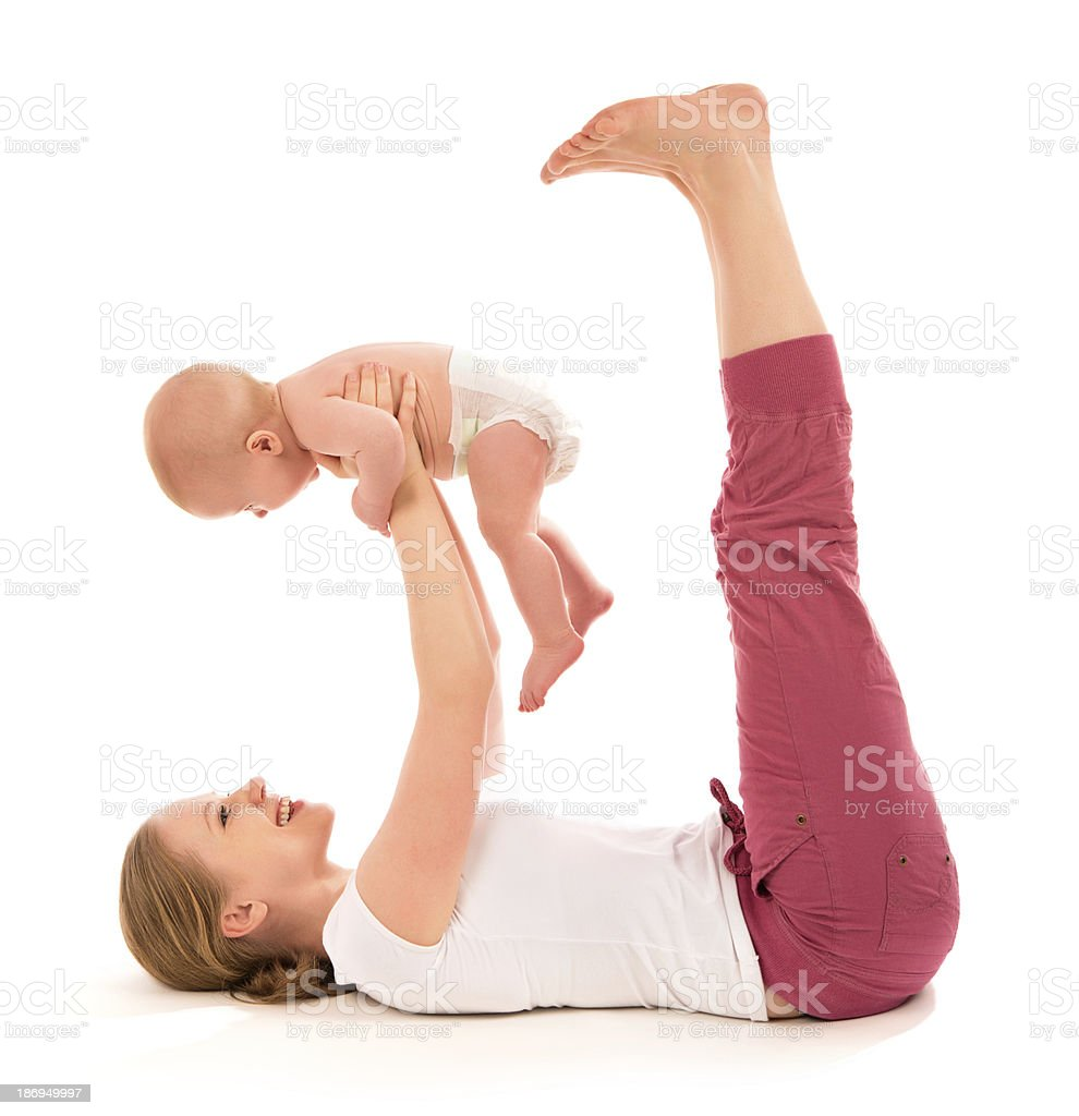 Smiling mother holding her baby while doing yoga stock photo
