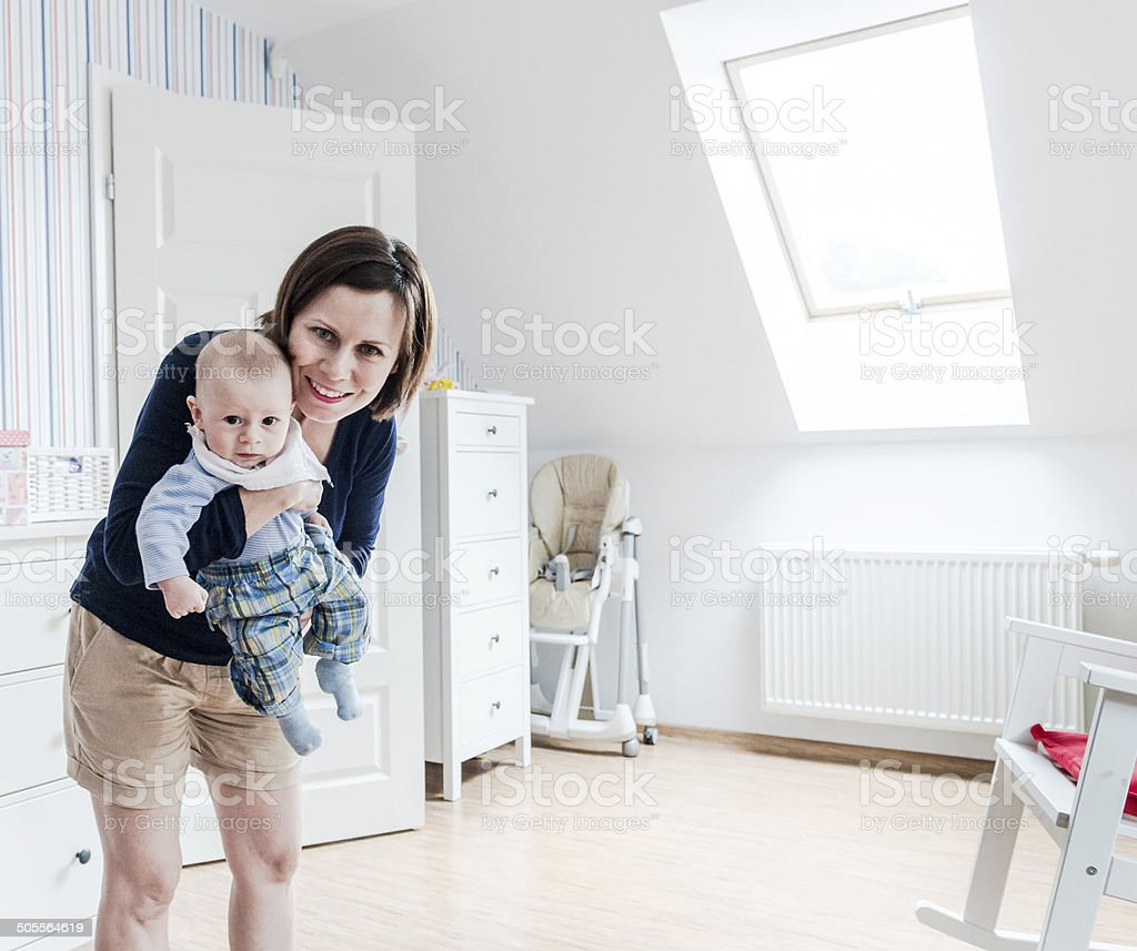 Smiling mother holding little baby boy on hands, baby's room stock photo