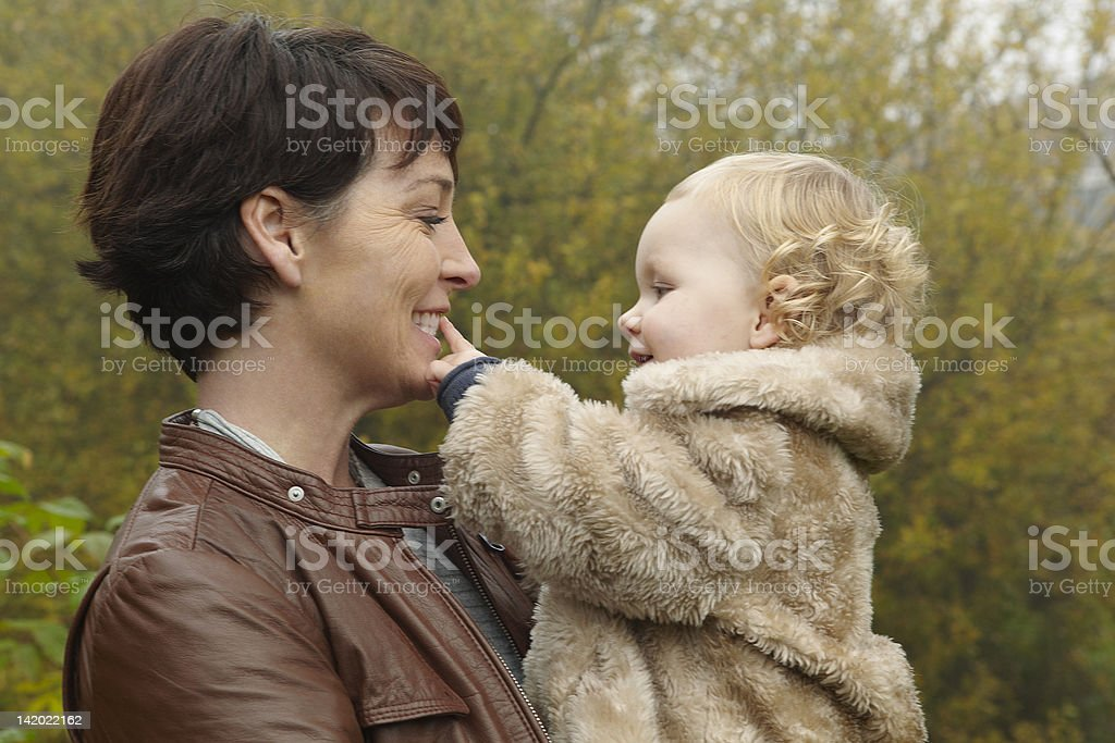 Smiling mother holding toddler outdoors stock photo