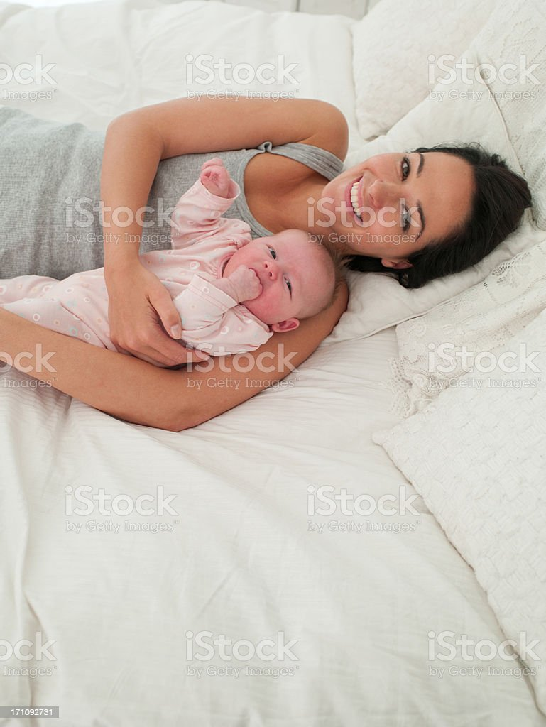 Smiling mother laying in bed with baby royalty-free stock photo