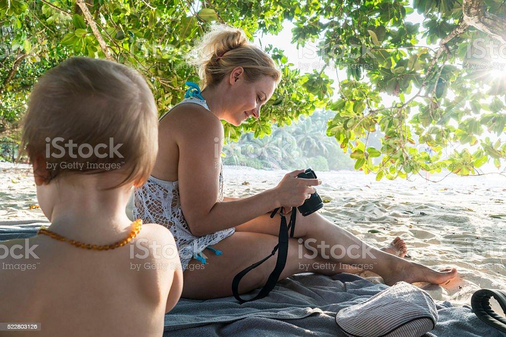 Smiling mother looking at summer vacation photos on digital camera. stock photo