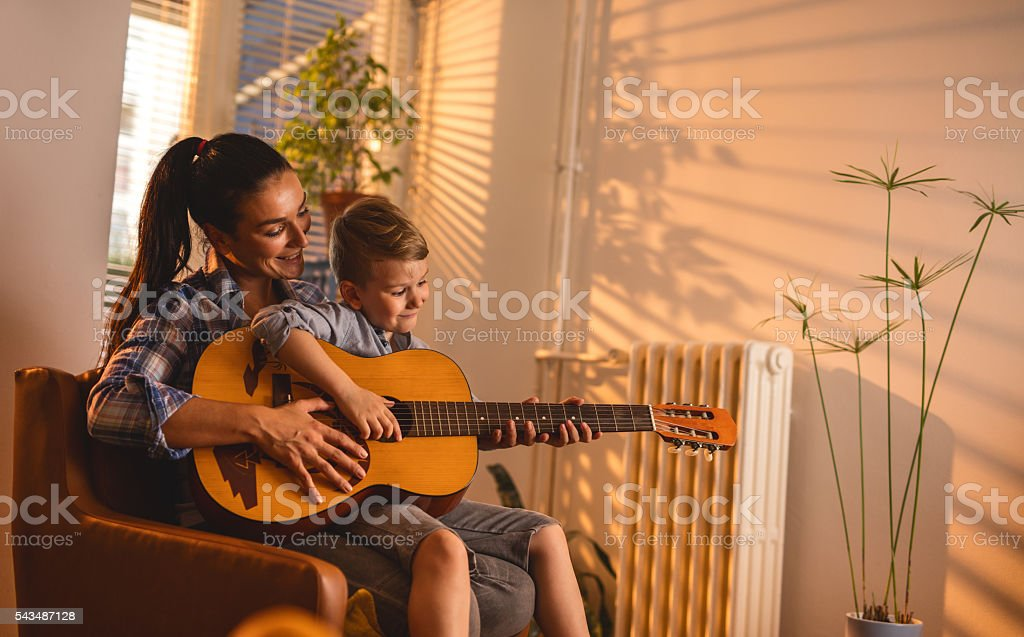 Smiling mother teaching her son to play acoustic guitar. stock photo