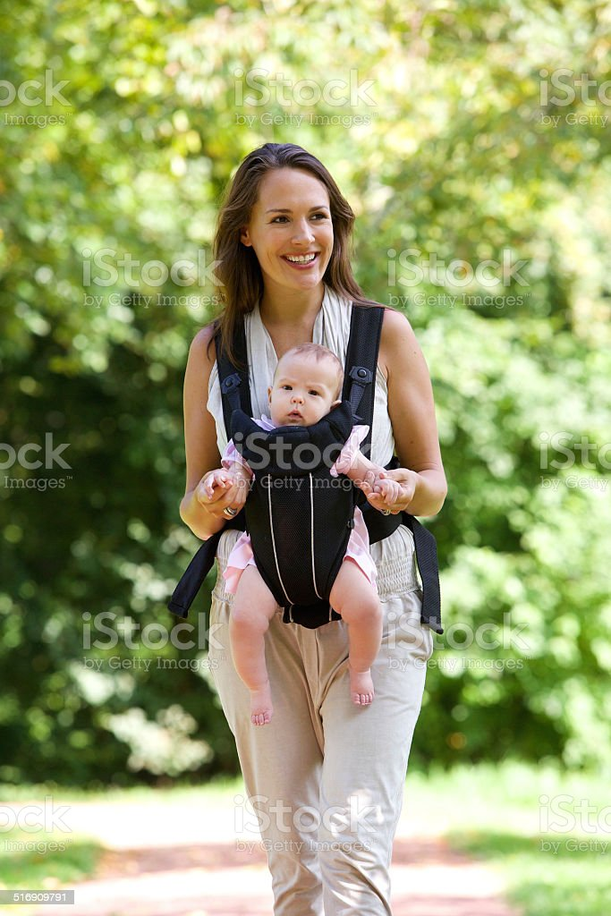 Smiling mother walking outdoors with baby in sling stock photo