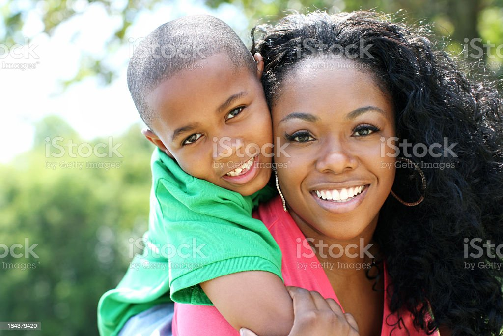 A smiling mother with her son over her shoulder royalty-free stock photo