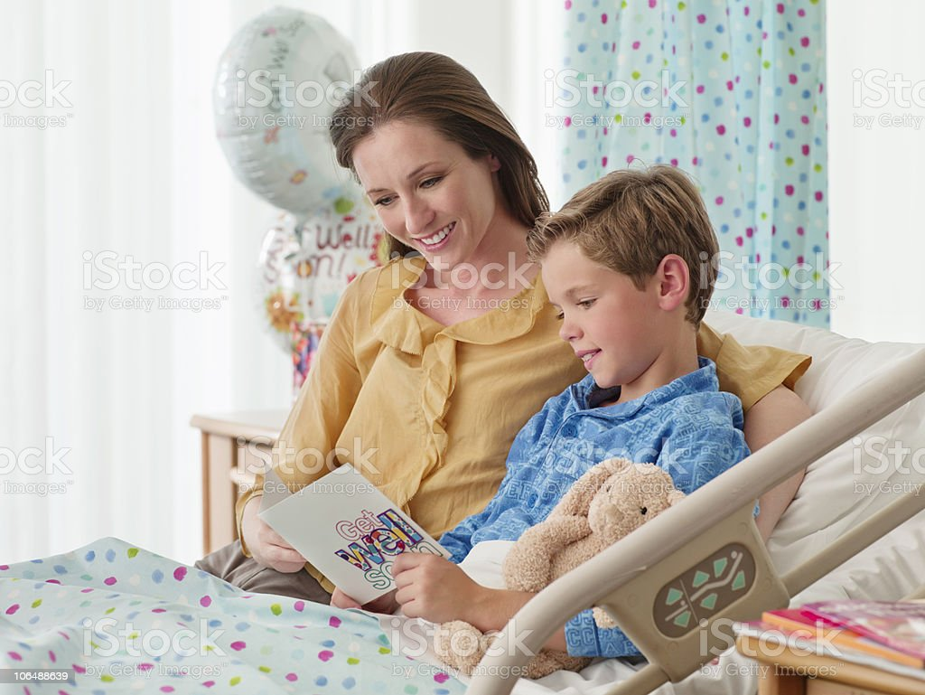 Smiling mother with son in bed (10-11) reading 'get well' card at hospital royalty-free stock photo