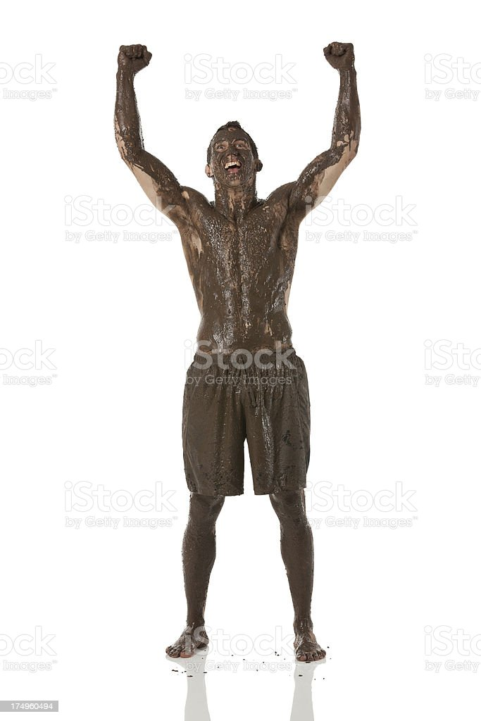 Smiling mud covered man standing with his arms raised royalty-free stock photo