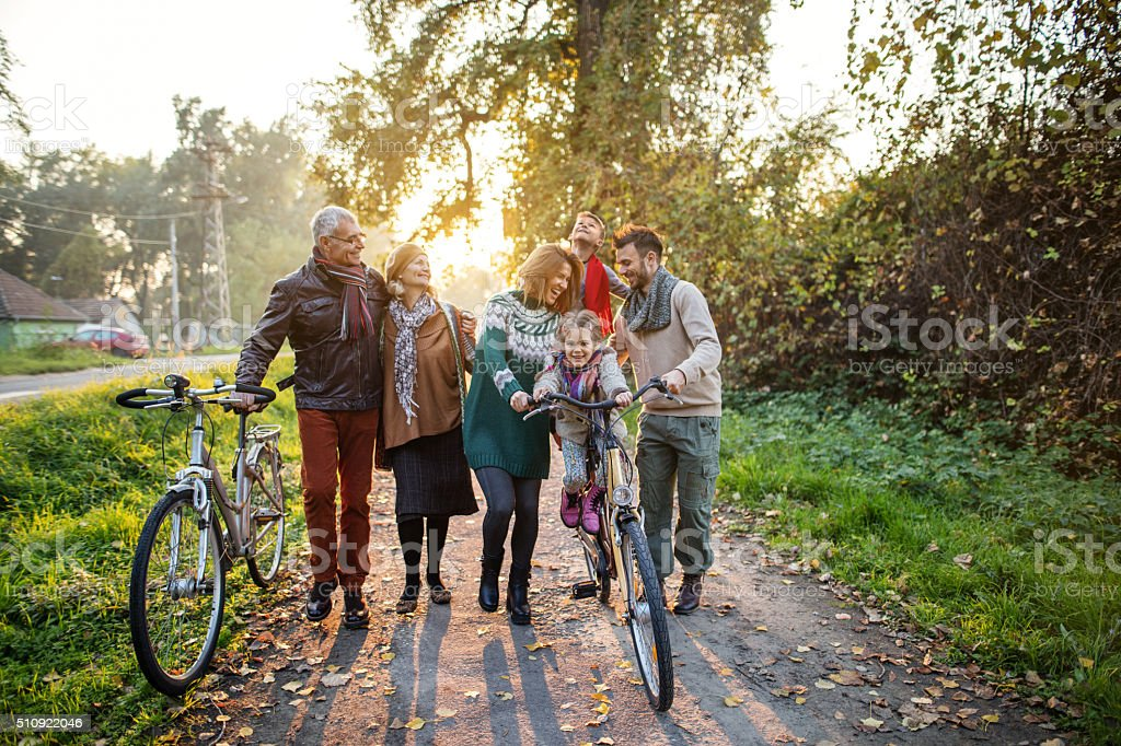 Smiling multi-generation family on bicycles in the park. stock photo