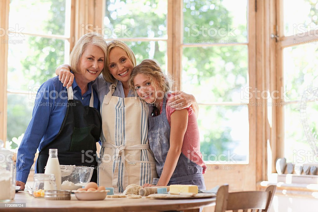 Smiling multi-generation females hugging in kitchen stock photo