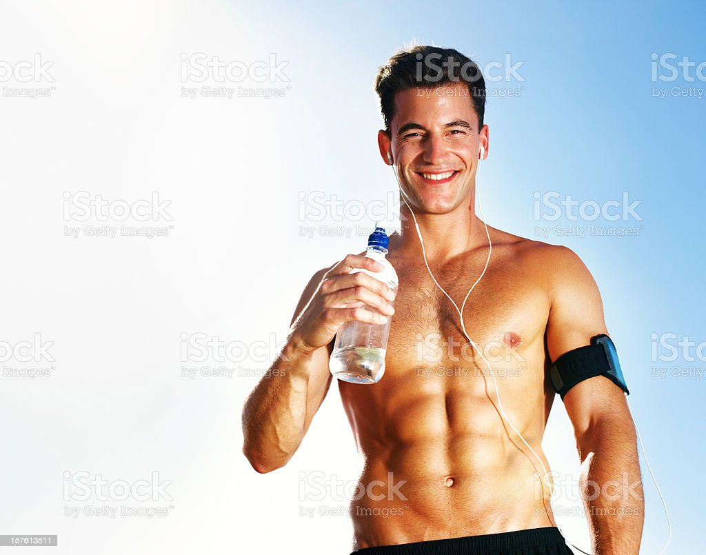 Smiling muscular guy holding a bottle while listening to music royalty-free stock photo