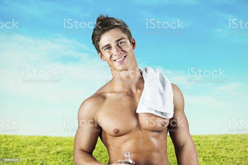 Smiling muscular man holding a water bottle royalty-free stock photo