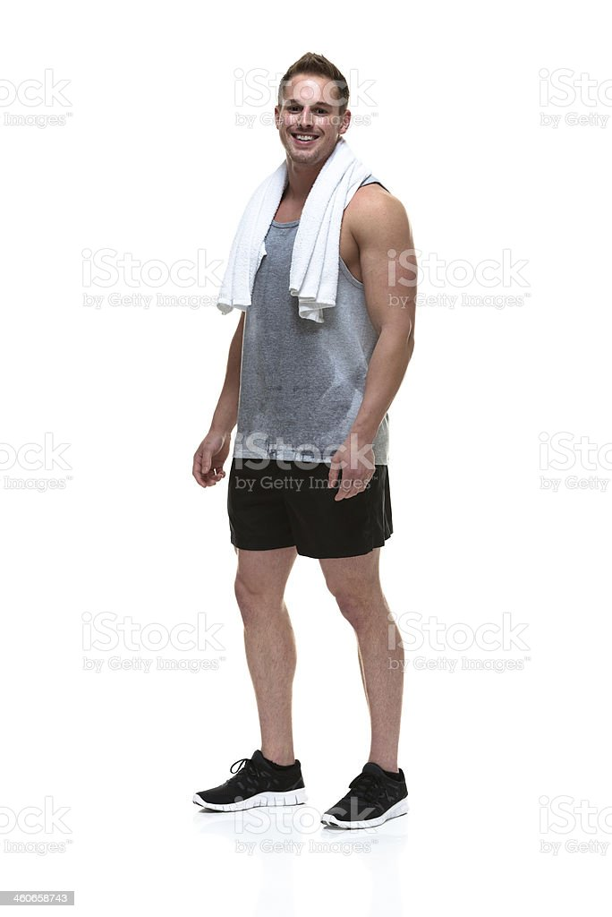 Smiling muscular man standing with towel on shoulder stock photo