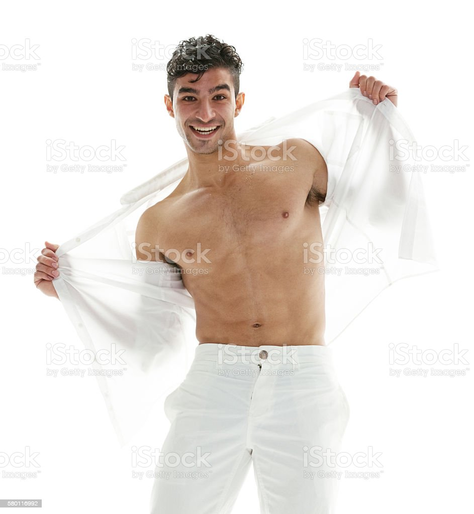 Smiling muscular man undressing stock photo