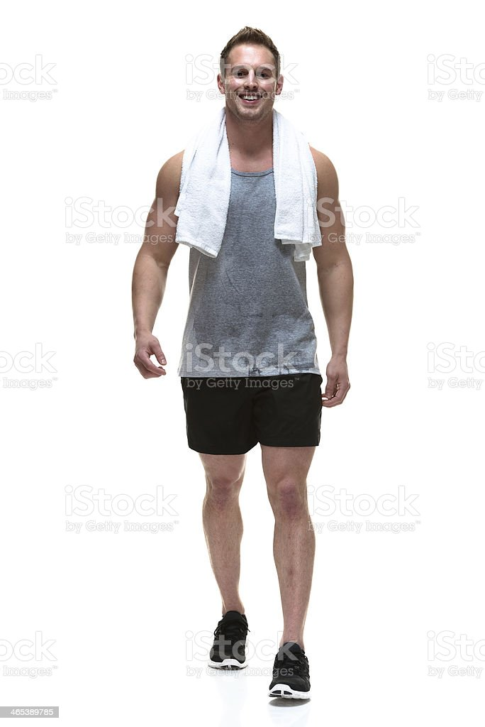 Smiling muscular man walking with towel on shoulder royalty-free stock photo