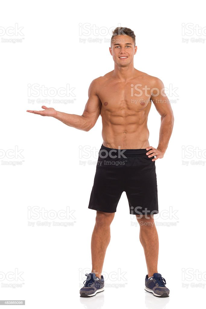 Smiling Muscular Young Man Presenting Product stock photo