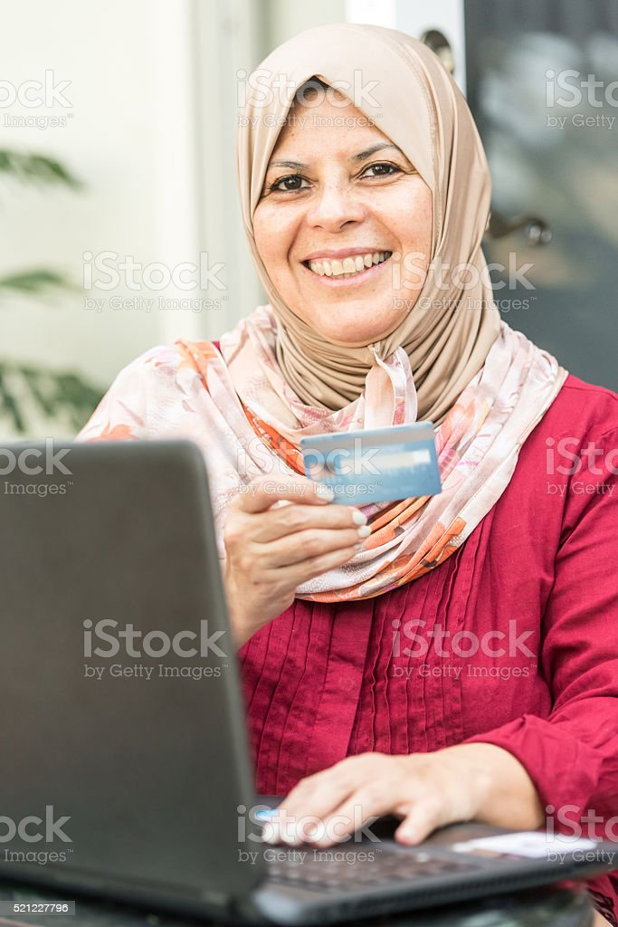 Smiling muslim shopping using the internet stock photo