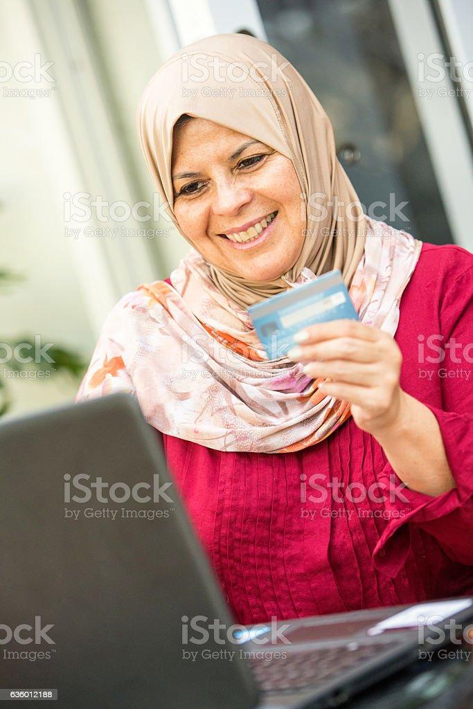 Smiling muslim shopping using the internet stock photo