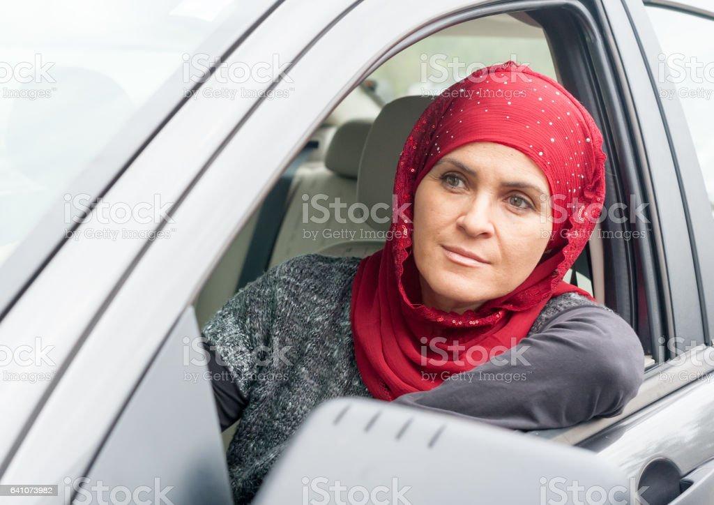 Smiling muslim woman driving stock photo