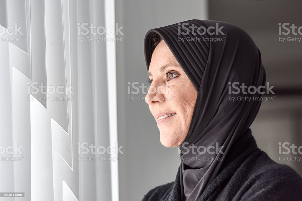 Smiling Muslim Woman looking through a Window stock photo